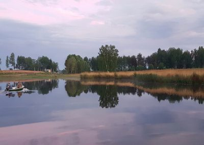 Лодка плывет по озеру Полевом - база отдыха Подворье